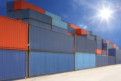Stack of cargo containers at container yard with sunbeam